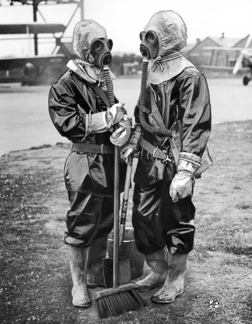 Navy, Army and Air Force are combining in coastal defense exercises which continued over a wide area of sea and land between Portsmouth and Plymouth, Devon. Among the innovations used, when an air raid black-out plunged Portsmouth into darkness was this new type of anti gas decontamination suit. It is absolutely air tight, and cannot be worn for more than 40 minutes. Ground engineers at an Air Force station near Portsmouth, Hampshire, on July 15, 1937, wearing the new decontamination suits in readiness for a raid. (Photo by AP Photo)