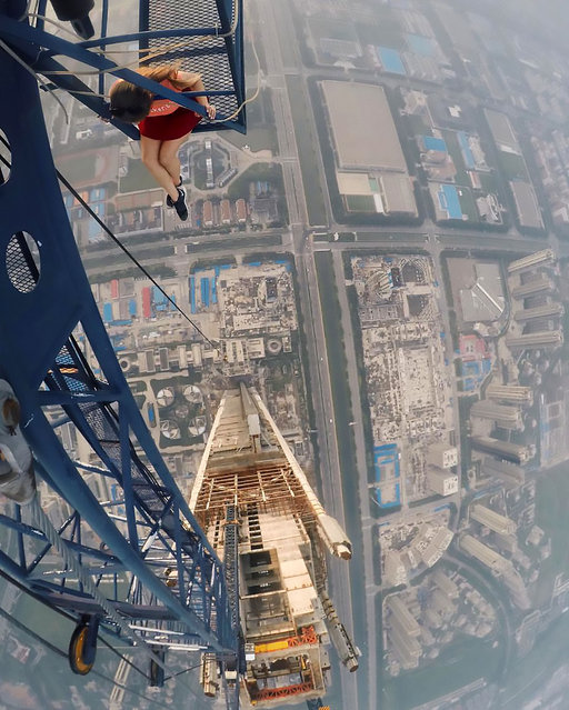 """An astonishing set of snaps of a thrill-seeker's sky-high catwalk show on the edge of some of the world's tallest buildings has turned her into a social media sensation. Daredevil Angelina Nikolau, 23, from Russia, has spent weeks travelling around China and Hong Kong posing for jaw-dropping skyscraper selfies hundreds of feet above the ground. Her vertigo inducing results – uploaded to Instagram – have made her an instant star on the internet. Angelina is described by Russian media as """"self-taught photographer, adventurer and roofer from Moscow"""". (Photo by Kirill Oreshkin/CEN)"""