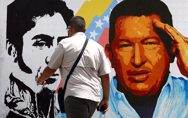 A man walks past a mural portraying the Venezuelan flag, President Hugo Chavez and South American liberator Simon Bolivar at the 23 de Enero neighbourhood, in Caracas on March 5, 2013. Venezuela plunged deeper into an uncertain future on Tuesday as cancer-stricken President Hugo Chavez took a turn for the worse, hit by a severe infection and breathing problems. Venezuelan Vice-President Nicolas Maduro expelled US Air Force Embassy attache David Del Monaco, giving him 24 hours to leave the country, accusing him of conspiracy. (Photo by Geraldo Caso/AFP Photo)