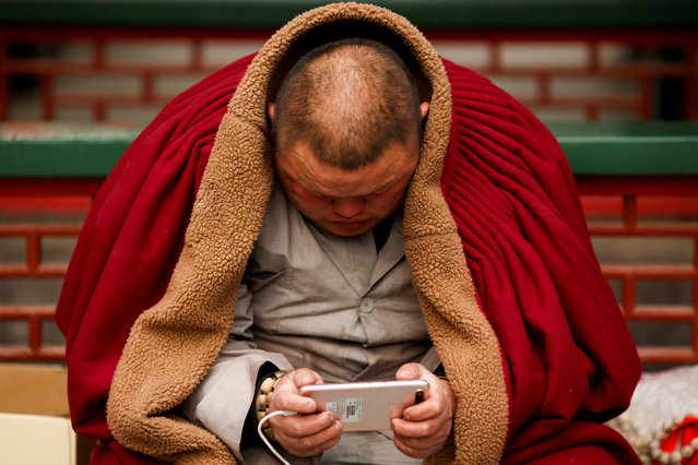 A man uses a smart phone at a Buddhist temple in Badachu park during Spring Festival celebrations marking Chinese New Year in Beijing, China, February 17, 2018. (Photo by Thomas Peter/Reuters)