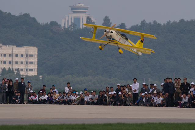 Spectators watch as a model aircraft performs an aerial display during the second day of the Wonsan Friendship Air Festival in Wonsan on September 25, 2016. (Photo by Ed Jones/AFP Photo)