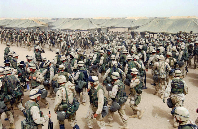 US Marines from the 2nd battalion/8 MAR, prepare themselves after receiving orders to cross the Iraqi border at Camp Shoup, northern Kuwait, on March 20, 2003. (Photo by Eric Feferberg/AFP Photo/The Atlantic)