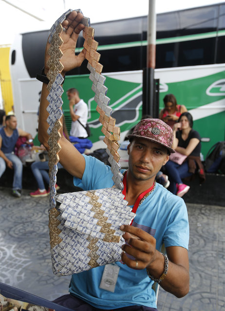 In this February 22, 2018 photo, Richard Segovia shows a bag he made with Venezuelan Bolivars in La Parada, Colombia, on the border with Venezuela. Segovia, 24, arrived two months ago, fleeing a dead-end job at a warehouse in Venezuela, where he made the equivalent of just $2.50 a month. (Photo by Fernando Vergara/AP Photo)