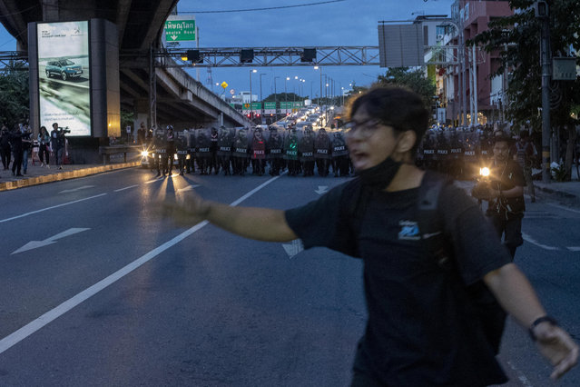A pro-democracy protester runs as riot police officers charge close to Government House in Bangkok, Thailand, Thursday, October 15, 2020. Riot Police disperse encampment of pro-democracy demonstrators who had camped out overnight after they had marched to Government House – the venue of the prime minister's office on Wednesday, Oct. 14. (Photo by Gemunu Amarasinghe/AP Photo)