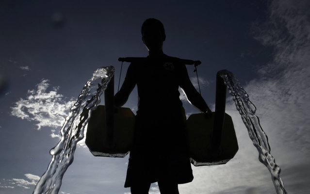 A farmer is silhouetted as he pours water, which he collected from a well, onto his bitter melon plants in Taguig City, Metro Manila, Philippines, on March 22, 2013. World Water Day falls on March 22. (Photo by Cheryl Ravelo/Reuters)