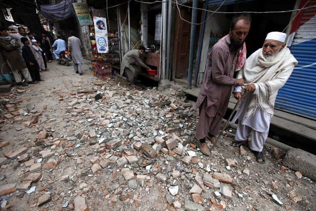 People stand in street covered with debris following a 7.7 magnitude earthquake, in Peshawar, Pakistan, 26 October 2015. (Photo by Arshad Arbab/EPA)