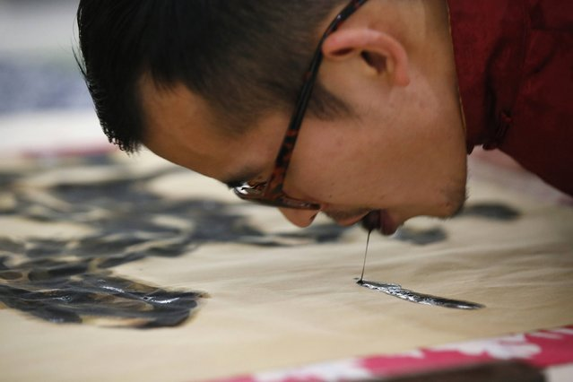Folk artist Han Xiaoming demonstrates painting with his tongue in Hangzhou, Zhejiang province December 4, 2014. (Photo by Aly Song/Reuters)