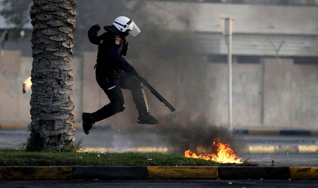 A policeman avoids petrol bombs thrown by anti-government protesters during clashes in Diraz, Bahrain, on April 1, 2013. The clashesl erupted after the funeral for Abdul Ghani  al-Rayes, who relatives and activists say collapsed and died outside of a police station where his son had been taken during a night of disturbances and arrests in Diraz. (Photo by Hasan Jamali/Associated Press)