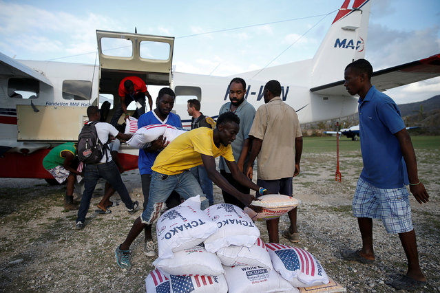 Men carry sacks of rice out from an airplane loaded with food at the airport after Hurricane Matthew passes Jeremie, Haiti, October 7, 2016. (Photo by Carlos Garcia Rawlins/Reuters)
