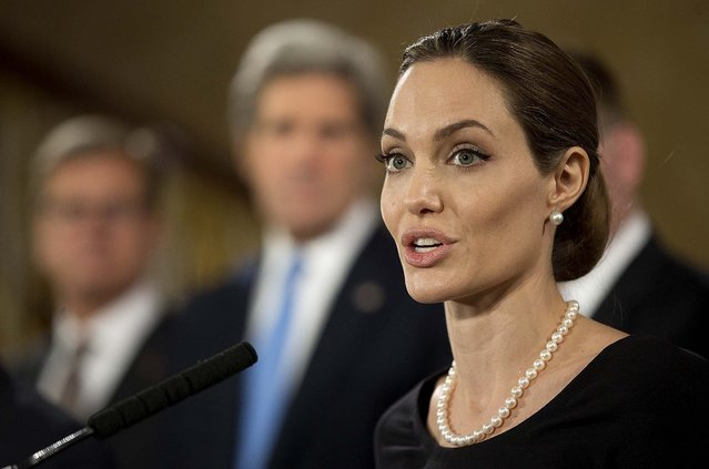 Flanked by G8 Foreign Ministers, Angelina Jolie, in her role as UN envoy, talks during a news conference regarding sexual violence against women in conflict, during the G8 Foreign Ministers meeting in London, on April 11, 2013. (Photo by Alastair Grant/Associated Press)