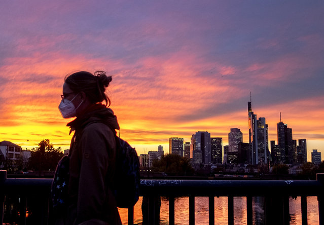 A woman wearing a face mask walks over a bridge with the buildings of the banking district in background in Frankfurt, Germany, Monday, October 26, 2020. (Photo by Michael Probst/AP Photo)