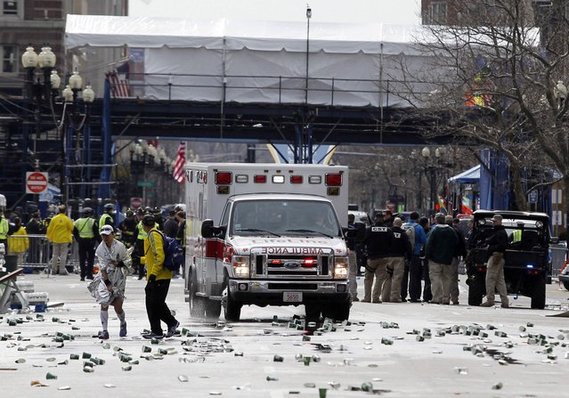 A runner is escorted from the scene after explosions went off at the 117th Boston Marathon in Boston, Massachusetts April 15, 2013. (Photo by Jessica Rinaldi/Reuters)