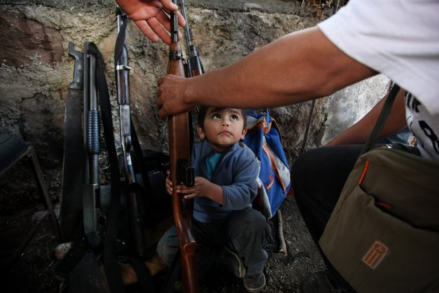 In this January 16, 2014 filephoto, a child tries to help his father arrange weapons at a checkpoint set up by the Self-Defense Council of Michoacan (CAM) in Tancitaro, Mexico. Authorities fear self-defense groups could turn into the very sort of organized crime forces they're fighting, while citizens who had been kidnapped, beaten and had land confiscated by the Knight Templar drug cartel praise the vigilantes for providing security. (Photo by Felix Marquez/AP Photo)