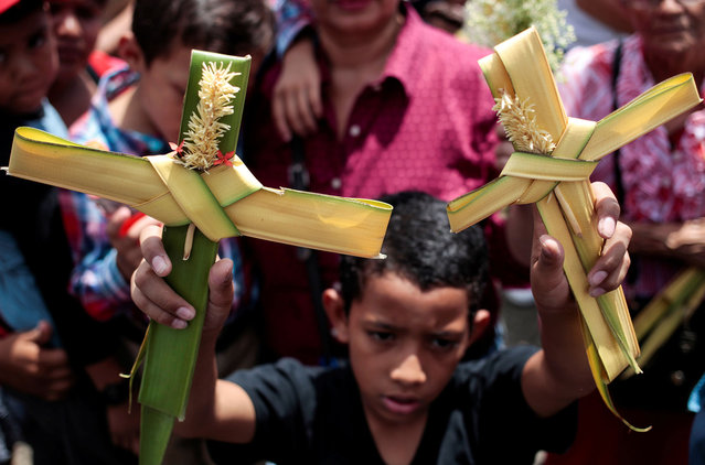 A boy holds up palm crosses during a Palm Sunday procession at the Metropolitan Cathedral in Managua, Nicaragua March 25, 2018. (Photo by Oswaldo Rivas/Reuters)