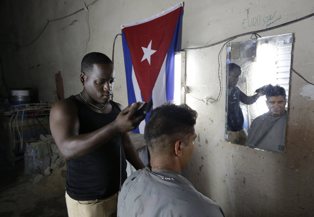 Adonis, a 17-year-old barber, cuts a customer's hair in his house in Havana, August 31, 2014. (Photo by Enrique de la Osa/Reuters)