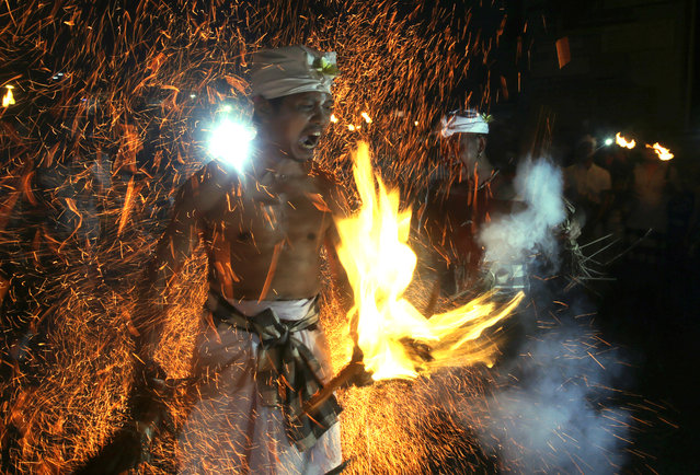 "A Balinese man is hit with flaming coconut leaves during the fire fight ritual called ""Lukat Gni"" before Nyepi, the annual day of silence marking Balinese Hindu new year in Klungkung, Bali, Indonesia, Friday, March 16, 2018. Bali's annual Day of Silence is so sacred that even reaching for a smartphone to send a tweet or upload a selfie to social media could cause offense. This year it will be nearly impossible to do that anyway, all phone companies have agreed to shut down the mobile internet for 24 hours on Saturday during the holiday that marks the New Year on the predominantly Hindu island. (Photo by Firdia Lisnawati/AP Photo)"