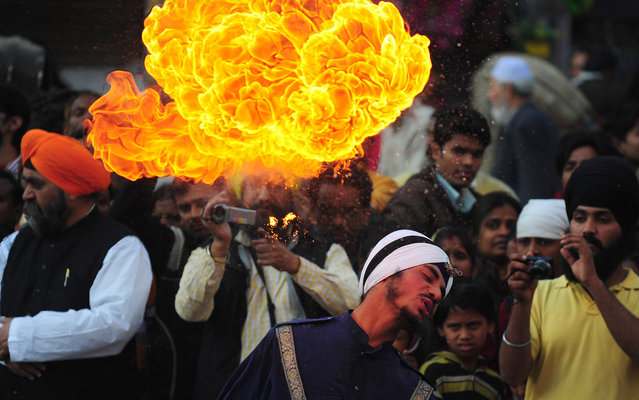 """Indian Sikh performers demonstrate their skills during a """"Nagar Kirtan"""" road show on the occasion of the three day event, """"Prakash Parv"""" ahead of the birth anniversary celebrations of Guru Gobind Singh in Allahabad on December 26, 2014. (Photo by Sanjay Kanojia/AFP Photo)"""