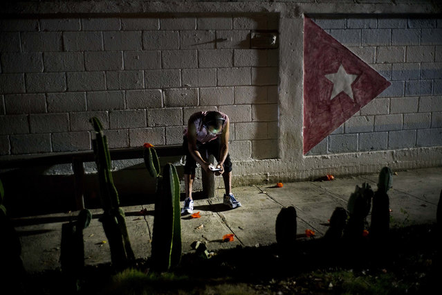 """In this April 14, 2018 photo, Lazaro Rodriguez, 42, connects his cell phone at a public internet hot spot at night in Havana, Cuba. Lazaro, who studied baking and is currently working in maintenance, said he's seen very positive changes in the economy in recent years, and would like to see development continue. """"The generation that comes after me will have much more. I lived 'the special period' in the 90s, and the country is still blocked"""", referring to the U.S. embargo. (Photo by Ramon Espinosa/AP Photo)"""