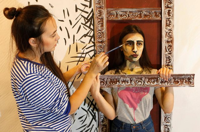 "Russian artist Maria Gasanova works with model Karina Magomedova on her ""The Alive Painting"" body art work during the Art Krasnoyarsk annual festival in Siberian city of Krasnoyarsk, Russia, October 26, 2016. (Photo by Ilya Naymushin/Reuters)"