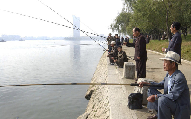 North Koreans fish on the bank of the River Taedong during an event held by the Central Committee of the Federation for the Care of the Elderly of Korea on the occasion of the 20th International Day of Old Persons in Pyongyang, October 1, 2010 in this picture released by the North Korea's KCNA news agency. (Photo by Jacky Chen/Reuters)