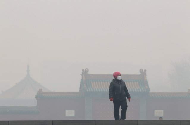 A woman wearing a mask walks outside the old palace museum on a hazy day in Shenyang, Liaoning province, November 8, 2015. As winter heating started in the city, the reading of PM2.5 was more than 1000 micrograms per cubic metre on Sunday, according to local media. (Photo by Reuters/Stringer)