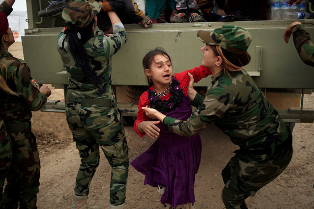 Kurdish female Peshmerga soldiers helps a newly internally displaced girl after she jumped from the truck upon her arrival at Al Khazar camp near Hassan Sham, east of Mosul, Iraq October 28, 2016. (Photo by Zohra Bensemra/Reuters)