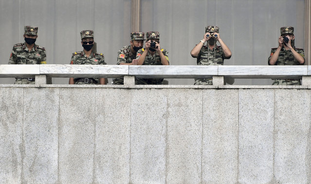In this September 16, 2020, file photo, North Korean army soldiers wearing face masks look at the South side during South Korean Unification Minister Lee In-young's visit to Panmunjom in the Demilitarized Zone, South Korea. North Korea is further toughening its restriction on the entry to sea as part of elevated steps to fight the coronavirus pandemic, state media said Sunday, Nov. 29, two days after South Korea said the North even banned fishing at sea. (Photo by Park Tae-hyun/Korea Pool via AP Photo/File)