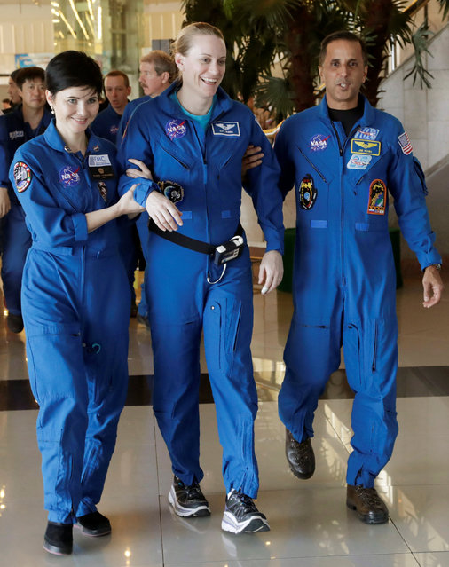 International Space Station (ISS) crew member Kate Rubins of the U.S. is assisted by NASA space agency specialists at the airport in Karaganda, Kazakhstan, October 30, 2016. (Photo by Dmitri Lovetsky/Reuters)