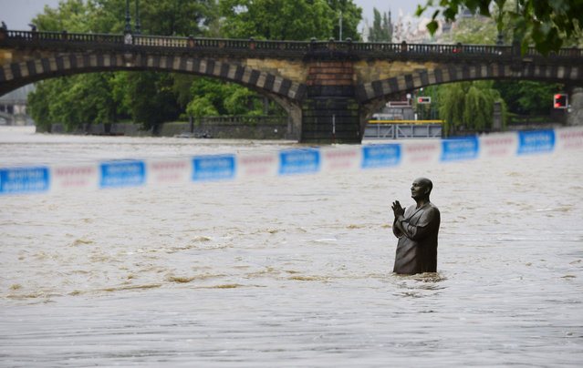 A flooded statue stands in the swollen Vltava river in the center of Prague, Czech Republic, Sunday, June 2, 2013. Heavy rainfalls cause flooding along rivers and lakes in Germany, Austria, Switzerland and the Czech Republic. (Photo by Roman Vondrous/AP Photo/CTK)