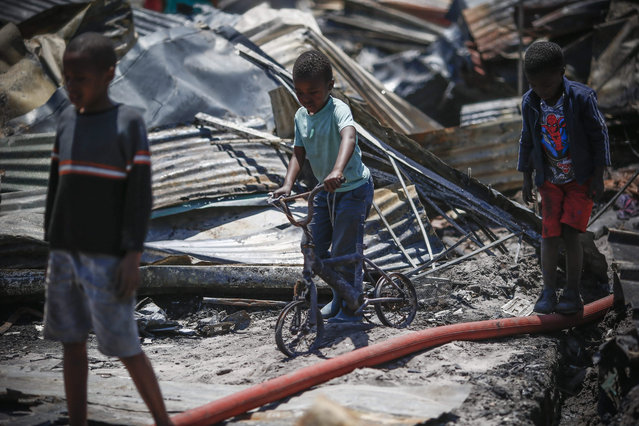 A South African boy and resident of Masiphumelele pushes the remains of his bicycle after a fire devistated parts of the informal shack settlement in Cape Town, South Africa, 29 November 2015. More than 800 shacks were destroyed and over 1000 residents displaced in the fire fanned by gale force winds which quickly spread in the overpopulated and dense shack settlement overnight. (Photo by Nic Bothma/EPA)
