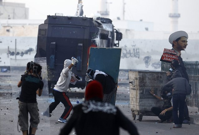 A protester throws a paint bottle at a riot police armoured personnel carrier during clashes in the village of Bilad al-Qadeem, south of Manama January 16, 2015. Protesters clashed with riot police as they called for the immediate release of Bahrain's main opposition party al-Wefaq's General Secretary Sheikh Ali Salman, who was arrested on December 28, 2014, after leading a protest rally against elections that were held in November and which his party boycotted, prompting U.S. criticism. (Photo by Hamad I. Mohammed/Reuters)