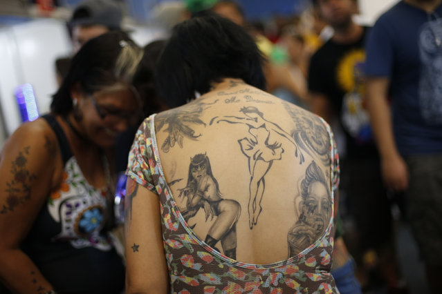 A woman whose back is covered in tattoos chats with friends during Rio Tattoo Week in Rio de Janeiro, Brazil, Friday, January 16, 2015. (Photo by Silvia Izquierdo/AP Photo)