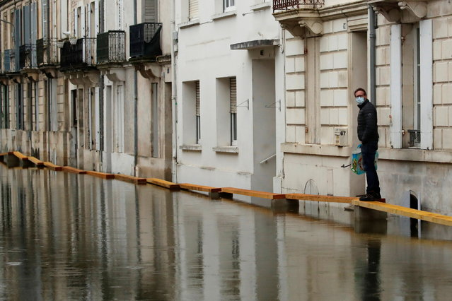 A resident walks on a makeshift walkway in a flooded area as the Charente River overflows in Saintes after days of rainy weather causing flooding in western France, France, February 8, 2021. (Photo by Stephane Mahe/Reuters)