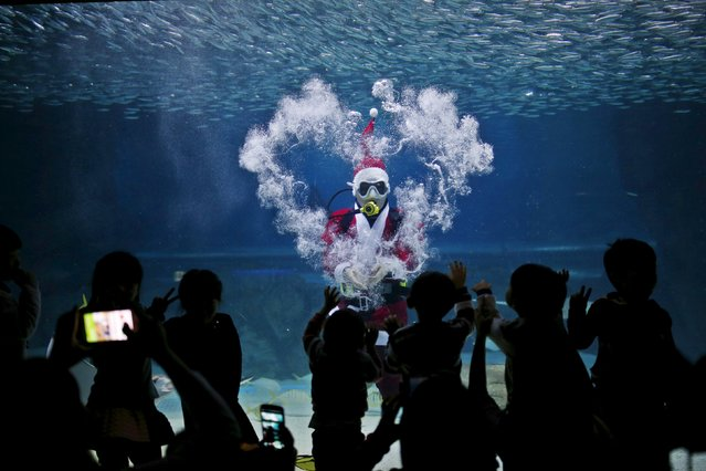 "A diver dressed in a Santa Claus costume makes heart-shape with bubbles as he swims with sardines during a promotional event for the Christmas ""Sardines Feeding Show with Santa Claus"" at the Coex Aquarium in Seoul, South Korea, December 9, 2015. (Photo by Kim Hong-Ji/Reuters)"