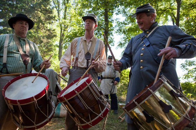 From left, Tommy White, Noah Raper and Jim Smith play drums during the 150th anniversary of the Battle of Gettysburg, Saturday, June 29, 2013, at Bushey Farm in Gettysburg, Pa. The Union Army stopped a major Confederate advance during a battle fought July 1-3, 1863, often considered the war's major turning point. (Photo by Zach Gibson/AP Photo/Richmond Times Dispatch)