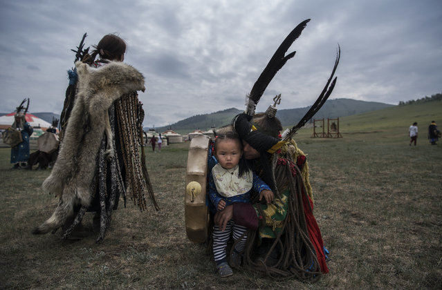 A Mongolian Shamans or Buu, sits with his child before a fire ritual meant to summon spirits to mark the period of the Summer Solstice June 23, 2018 outside Ulaanbaatar, Mongolia. (Photo by Kevin Frayer/Getty Images)
