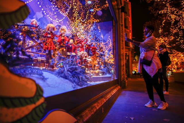 A woman takes a picture of a window display at the Printemps department store where lights are switched on for the Christmas season in Paris, France, November 17, 2020. (Photo by Benoit Tessier/Reuters)