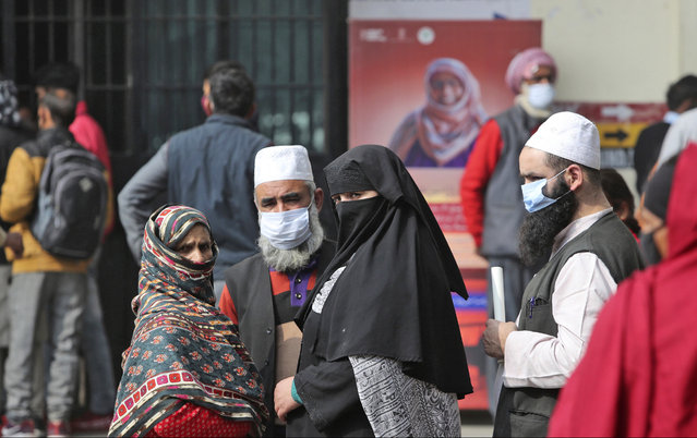 People wearing face masks as a precaution against the coronavirus wait outside a government hospital in Jammu, India, Tuesday, February 16, 2021. (Photo by Channi Anand/AP Photo)