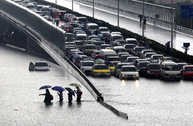This picture taken on July 7, 2013 shows people walking through a flooded street in Wuhan, central China's Hubei province after a heavy storm. A strong storm hit Wuhan on July 6 and July 7, paralysing transport in multiple places, local media reported. (Photo by AFP Photo)