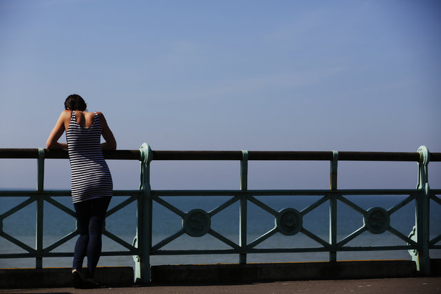 A woman looks out to sea in the sunny weather on Brighton beach in southern England May 16, 2014. (Photo by Luke MacGregor/Reuters)
