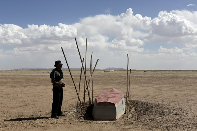 Fisherman Valerio Huanca stands next to a boat on the dried Poopo lakebed in the Oruro Department, south of La Paz, Bolivia, December 17, 2015. (Photo by David Mercado/Reuters)