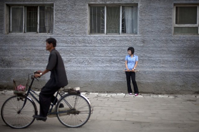 In this Friday, June 21, 2013 photo, a woman stands on a street as a man cycles past in Haeju city, in South Hwanghae Province, North Korea. (Photo by Alexander F. Yuan/AP Photo)