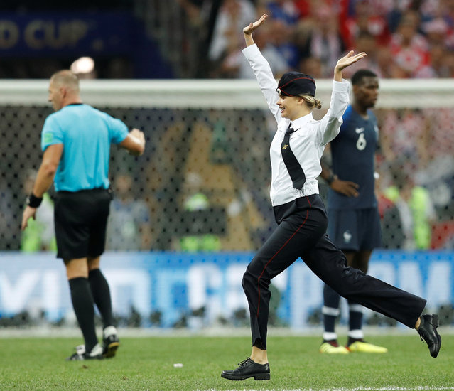 "A pitch invader during the 2018 FIFA World Cup Final between France and Croatia at Luzhniki Stadium on July 15, 2018 in Moscow, Russia. p*ssy Riot claimed responsibility for the pitch invasion, tweeting: ""Just a few minutes ago four p*ssy Riot members performed in the FIFA World Cup final match – «Policeman enters the Game»"". (Photo by Darren Staples/Reuters)"