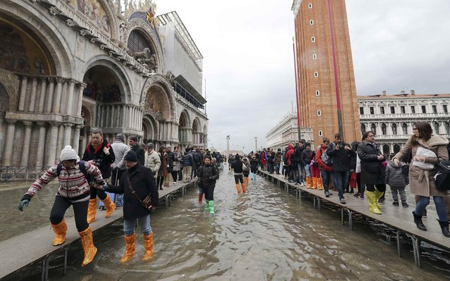 Tourists walk on raised platforms above flood waters during a period of seasonal high water and on the first day of carnival, in Venice February 1, 2015. (Photo by Stefano Rellandini/Reuters)