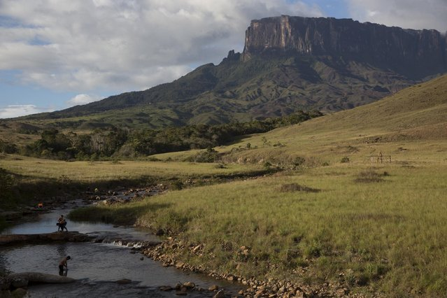 People bathe on the Tec river as they are on the road to Mount Roraima, near Venezuela's border with Brazil January 13, 2015. While that is a help to Venezuela's tottering tourism industry and brings revenues to local communities, it is also scattering a prehistoric landscape with unwanted litter. (Photo by Carlos Garcia Rawlins/Reuters)