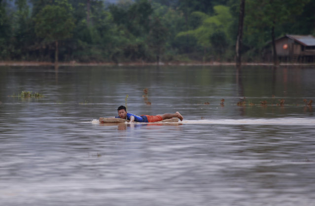 A man swims with matress in flooded village in Sanamxay district, Attapeu province, Laos, Thursday, July 26, 2018. (Photo by Hau Dinh/AP Photo)