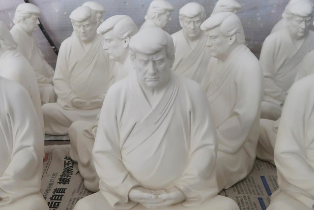 Statues depicting former U.S. President Donald Trump in a Buddhist meditative pose, by Chinese designer Hong Jinshi, are seen at a workshop in Dehua, Fujian province, China on March 24, 2021. (Photo by Martin Pollard/Reuters)