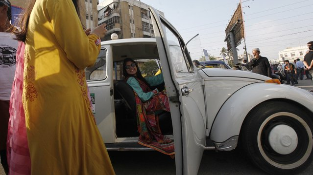 "A visitor sits in a Volkswagen Beetle car while being photographed by her friend during the 3rd annual ""Classic Volkswagen Show"" in Karachi February 1, 2015. Around 100 cars and jeeps were displayed at the classic Volkswagen car show organized by the Motorheads Pakistan and Volkswagen Club of Pakistan. (Photo by Akhtar Soomro/Reuters)"