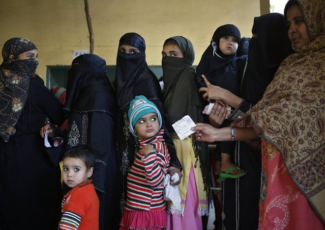 Voters stand with their children in a queue to cast their votes at a polling station during the state assembly election in New Delhi February 7, 2015. (Photo by Anindito Mukherjee/Reuters)