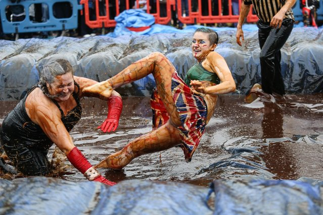 Two brave contestants take part in the World Gravy Wrestling Championships at the Rose 'n Bowl in Stacksteads, Lancashire, England on August 27 2018. (Photo by The Mercury Press)